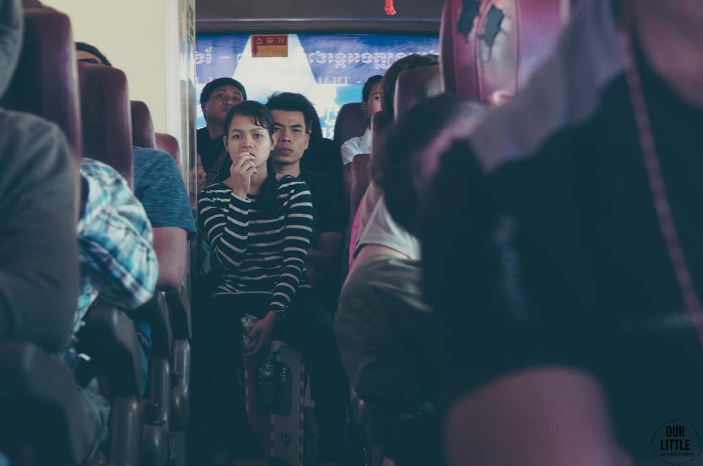 Ludzie siedzący na plastikowych wiaderkach w przejściu w autobusie z Tajlandii do Kambodży