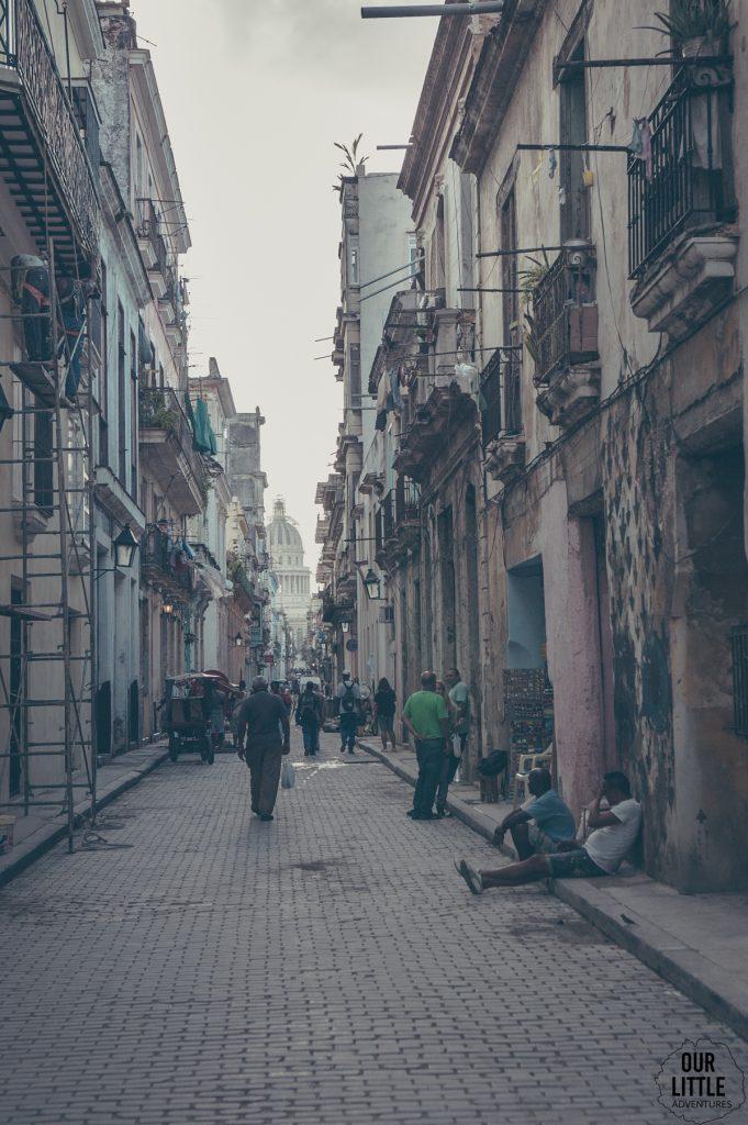 Zdewastowana ulica Hawany, z widocznymi ludźmi siedzącymi na chodniku oraz rusztowaniami. W oddali widoczny budynek Capitolu