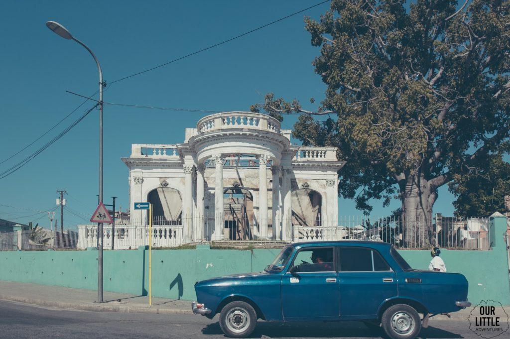 niebieski samochód zaparkowany przed zniszczonym kolonialnym pałacem w Santiago de Cuba