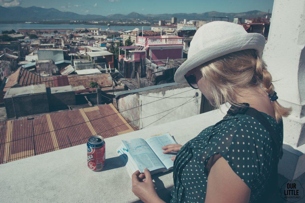 Kobieta czytająca przewodnik Lonely Planet po Kubie z widokiem na miasto