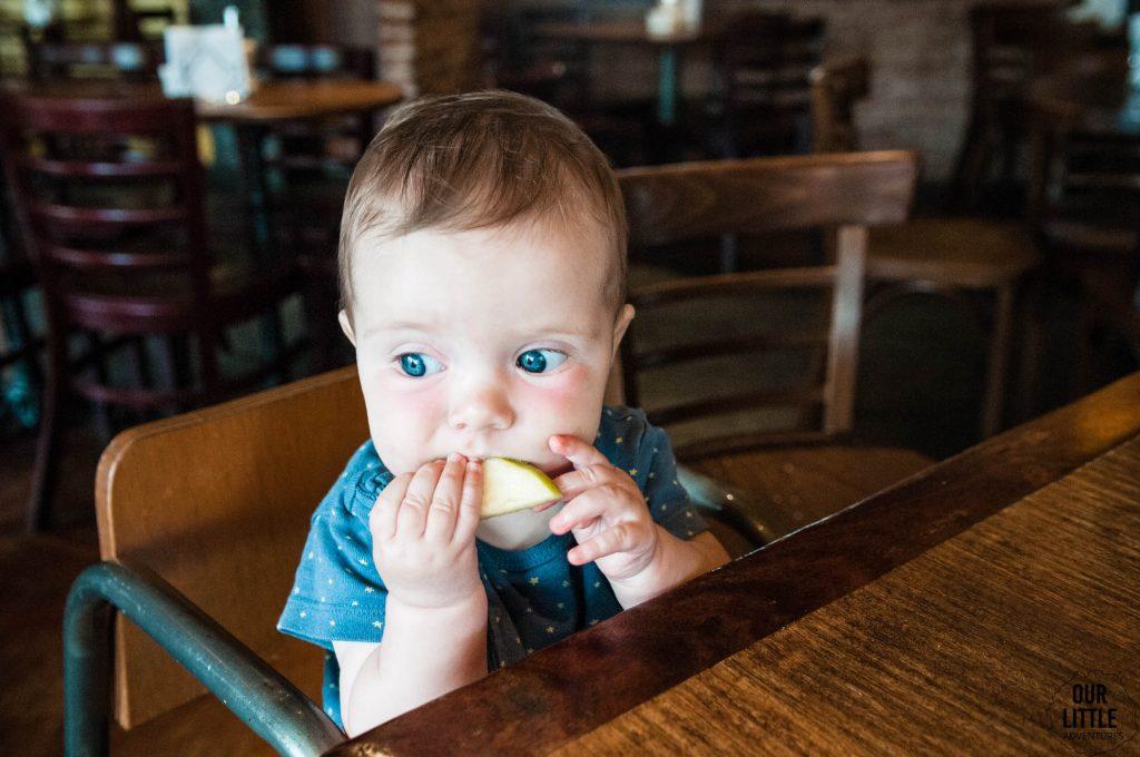 Dziecko jedzące kawałek jabłka, siedząc przy stoliku w restauracji