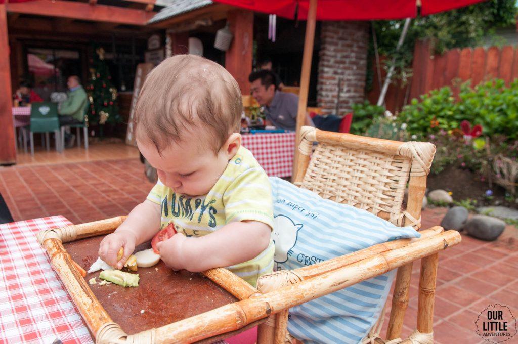 dziecko siedzące w krzesełku przy stole próbujące chwycić awokado w rączkę