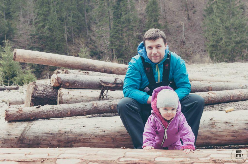 Mężczyzna siedzący na balach drewna z dzieckiem które opiera się drewno
