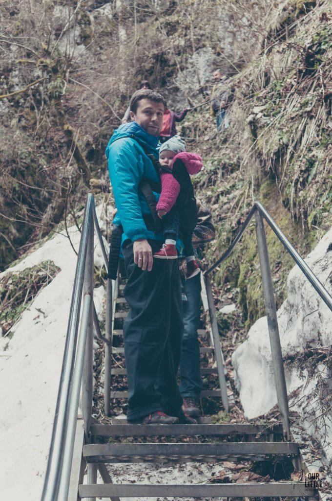 Mężczyzna z dzieckiem w nosidle, stoi na schodach w wejściu do jaskini