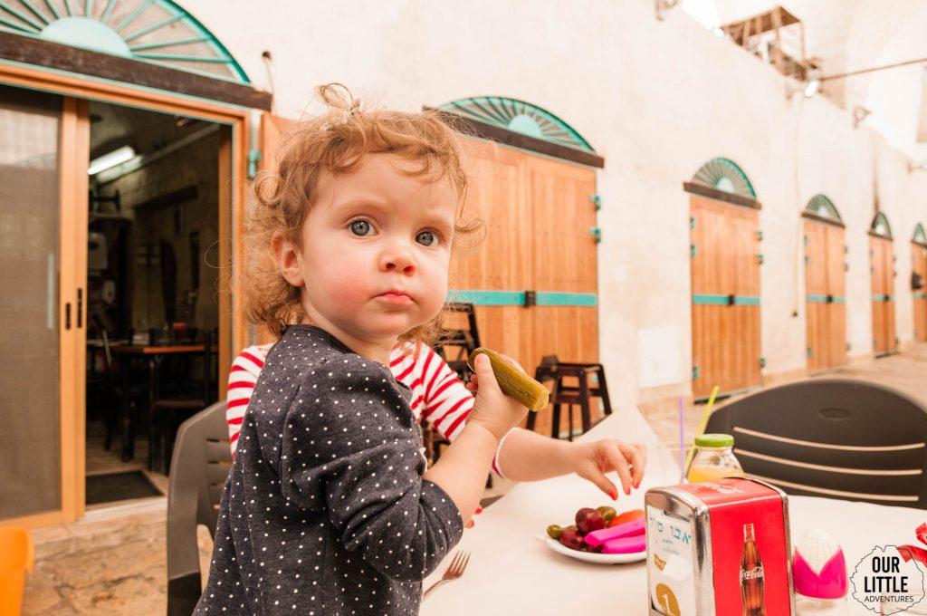Mania w restauracji w Akka trzyma w rączce ogórka kiszonego