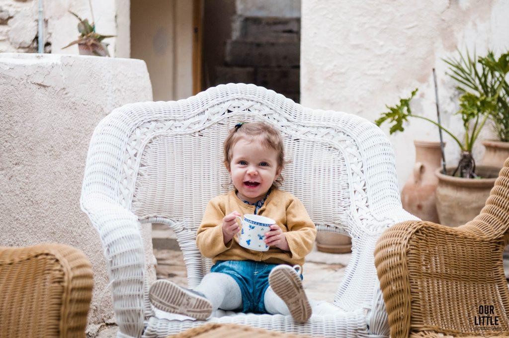 Mania pije ciepłe mleko siedząc na wiklinowym fotelu