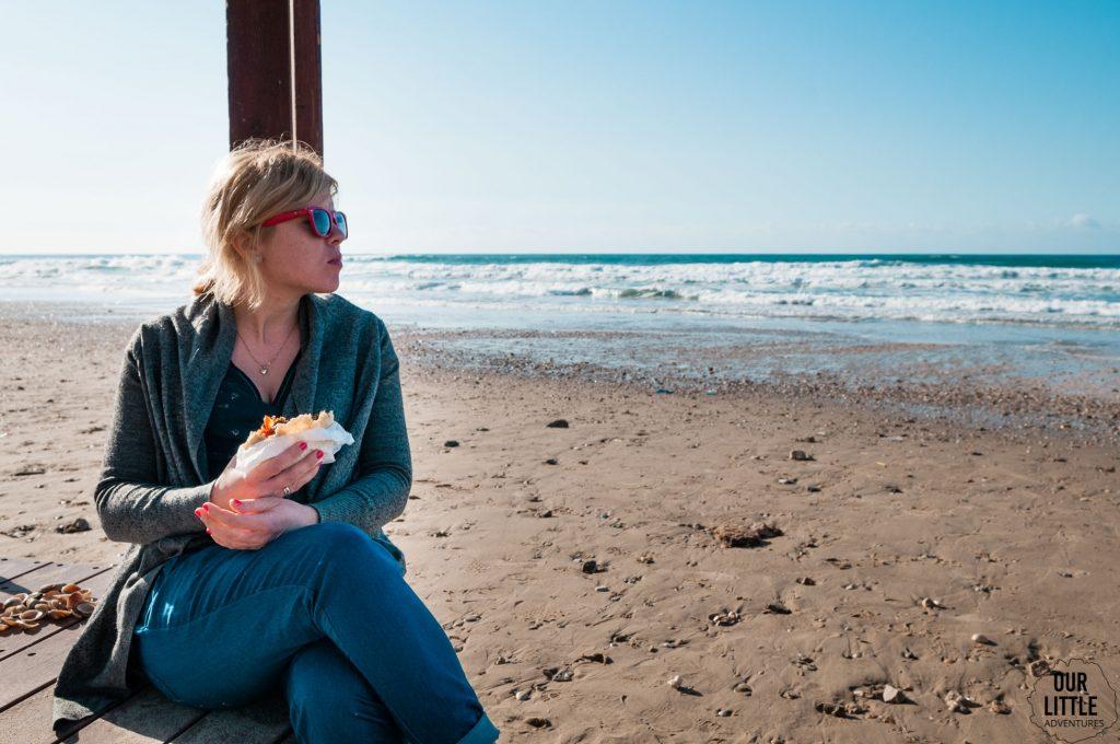 Karolina siedzi na plaży w Tel-Awiwie i je shoramę