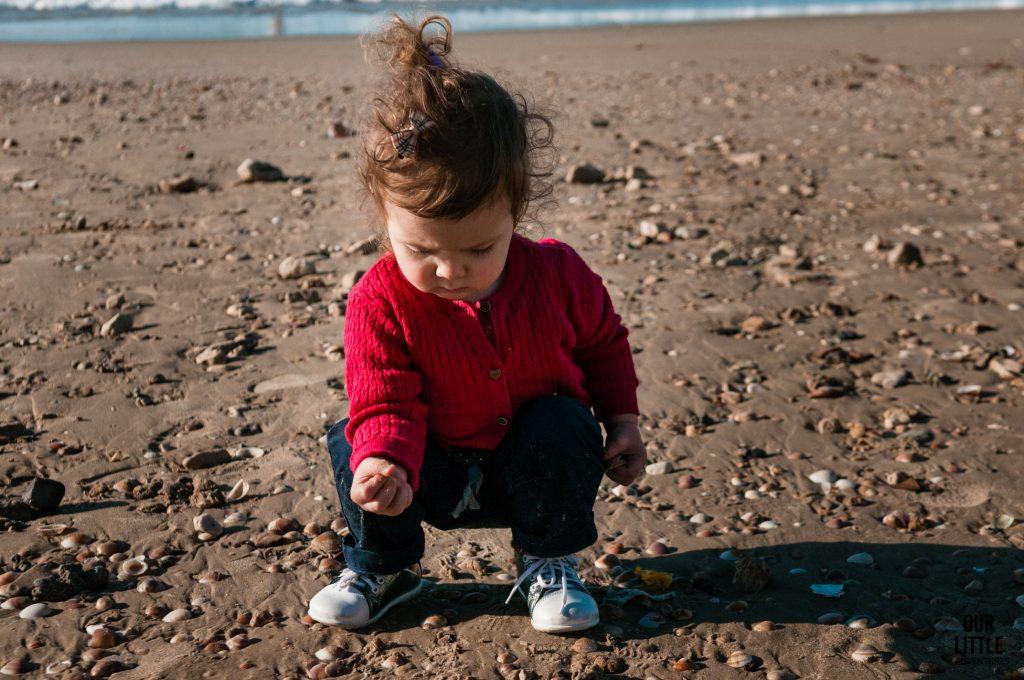 Marianka kuca na plaży w Tel-Awiwie i zbiera muszelki