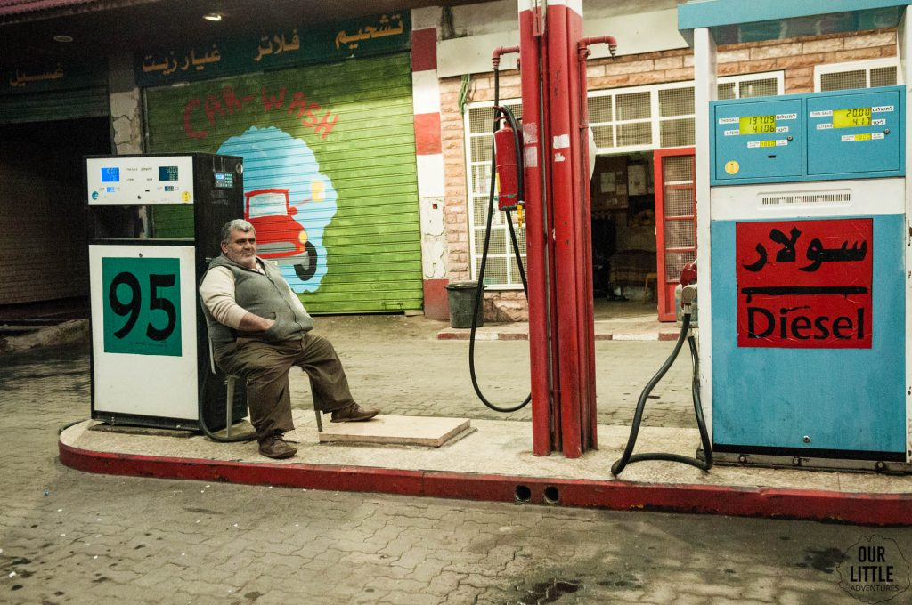 Facet siedzący na stacji benzynowej między dystrybutorami w Betlejem