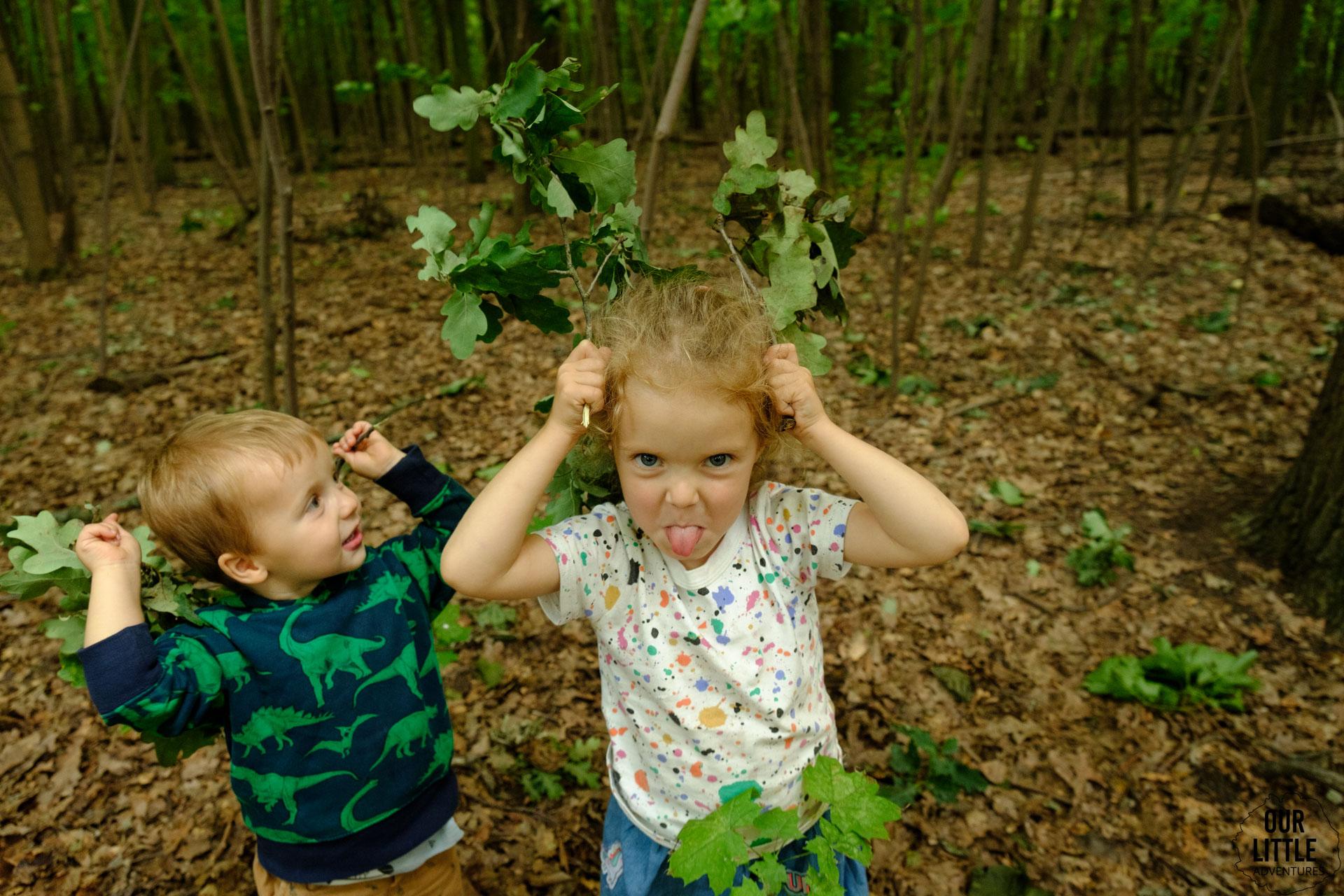 Jasia i Marianna trzymają przy uszach gałązki z liśćmi
