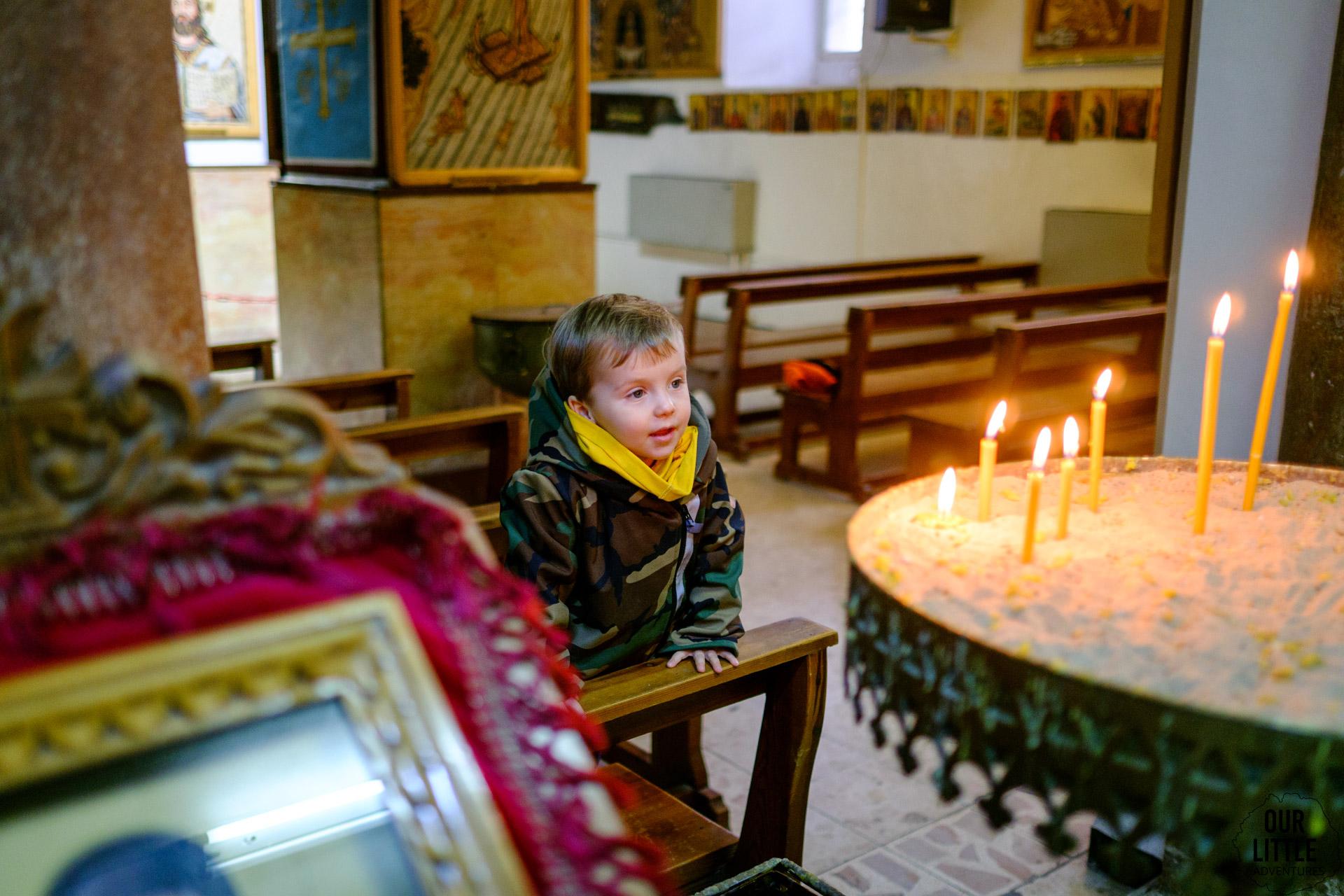 Jasio przygląda się świeczkom w cerkwi św. Jerzego w Madabie