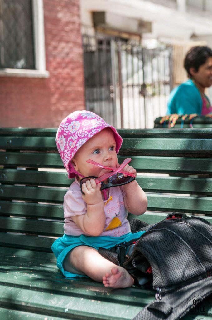 dziecko w różowej czapce siedzące na ławce, gryzące okulary przeciwsłoneczne
