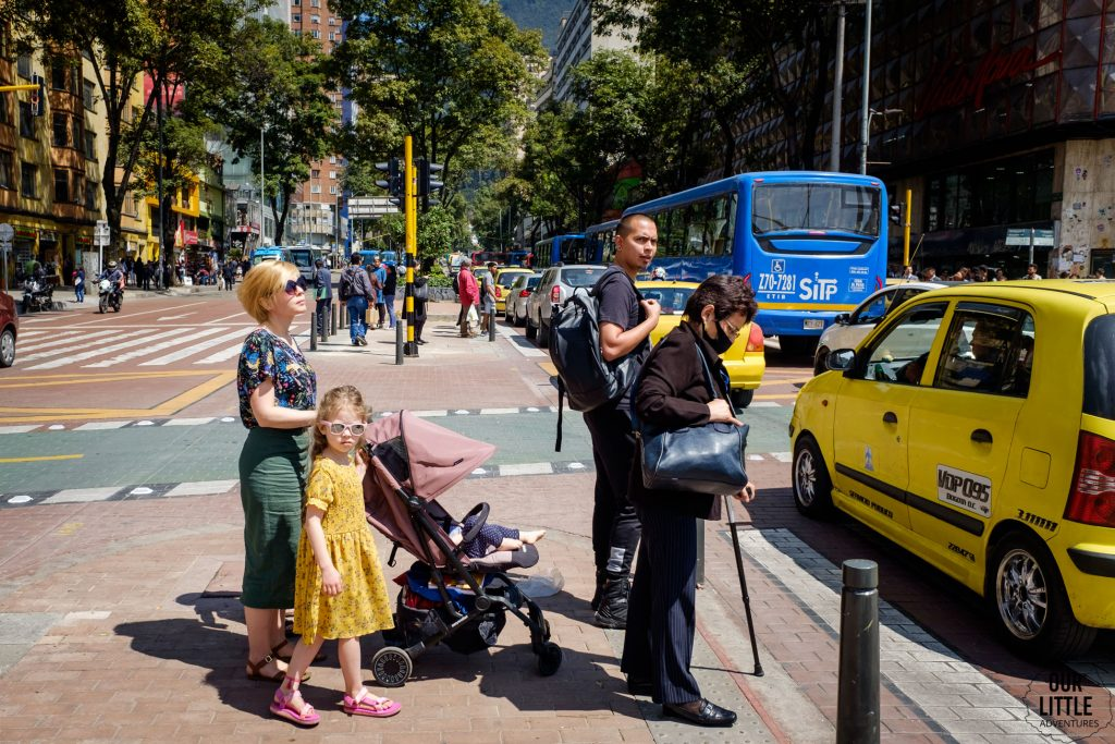 Kobieta z wózkiem i trójką dzieci stoi na przejściu dla pieszych w Bogocie