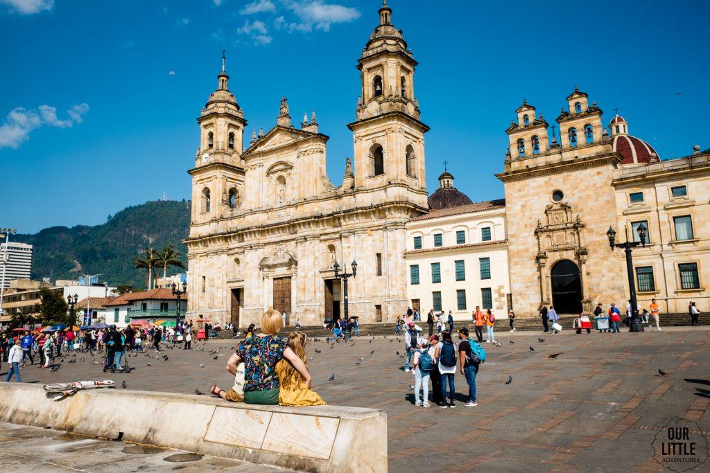 Kobieta z dziećmi siedzi na murku na placu Simona Bolivara, w tle katedra