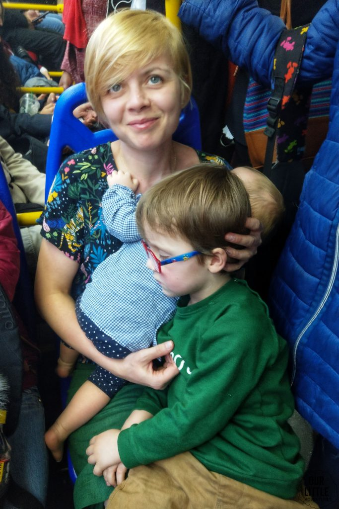 Karolina trzyma na rękach Barbarę i na kolanach Jasia oboje śpiących w Transmilenio