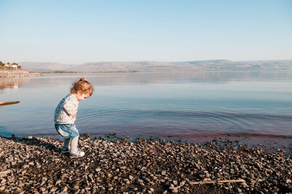 Mania szukająca kamieni na brzegu jeziora Galilejskiego