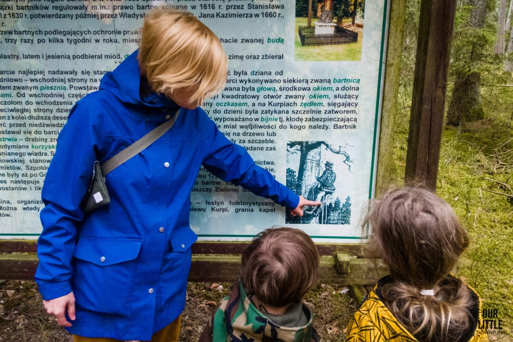 Karolina wyjaśnia dzieciom, przy tablicy inforamcyjnej, kto to bartnicy