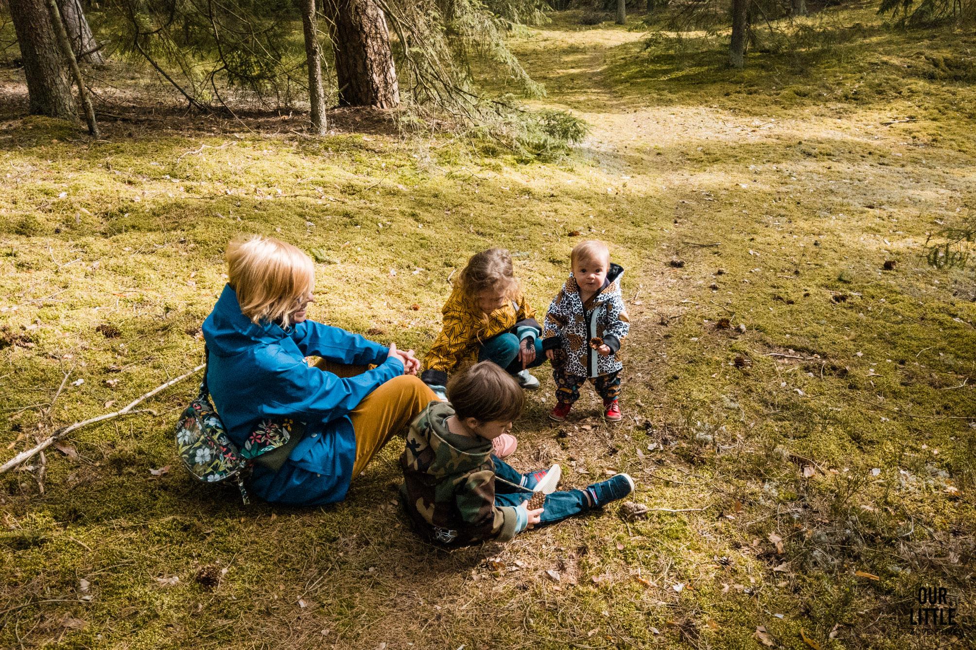Matka z trójką dzieci siedzi na ziemi w lesie w Puszczy Zielonej
