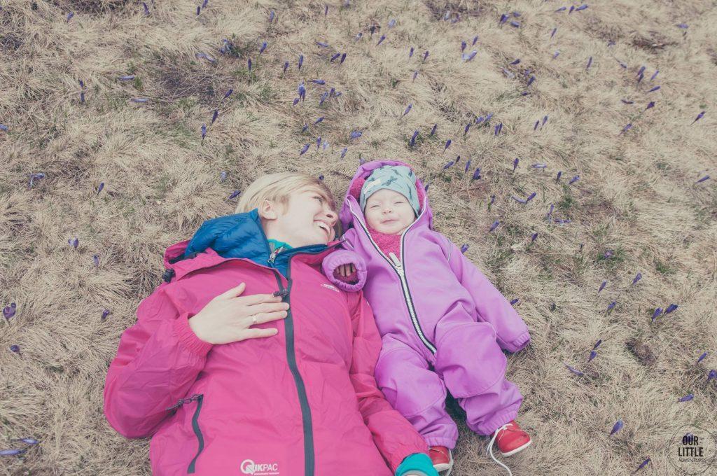 Mama z córką leżą na trawie wśród krokusów