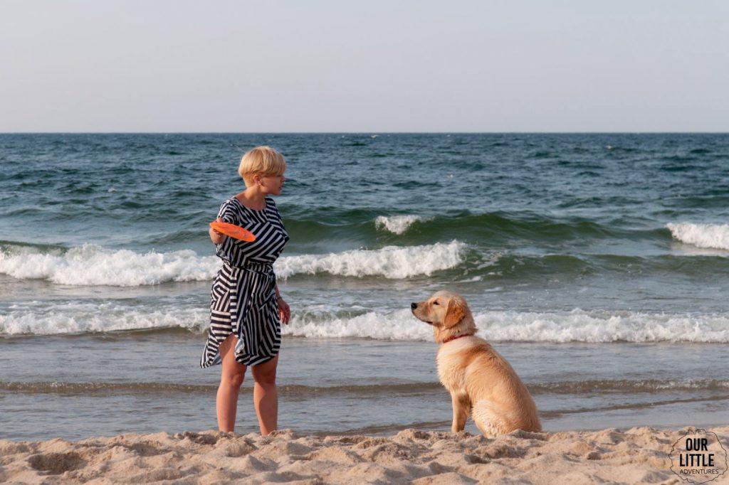 Kobieta i pies na plaży we Władysławowie. Kobieta ma zamiar rzucić frisbee