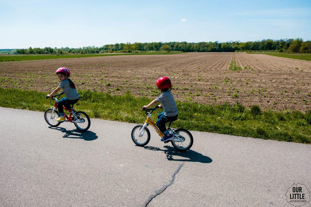 Mania i Jasio na ścieżce rowerowej do parku w Powsinie. Jadą na rowerach Woom