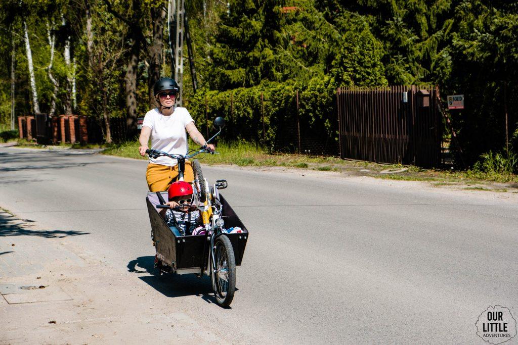 Karolina jedzie na rowerze cargo Stork a w skrzyni siedzi Jasio z rowerem Woom2