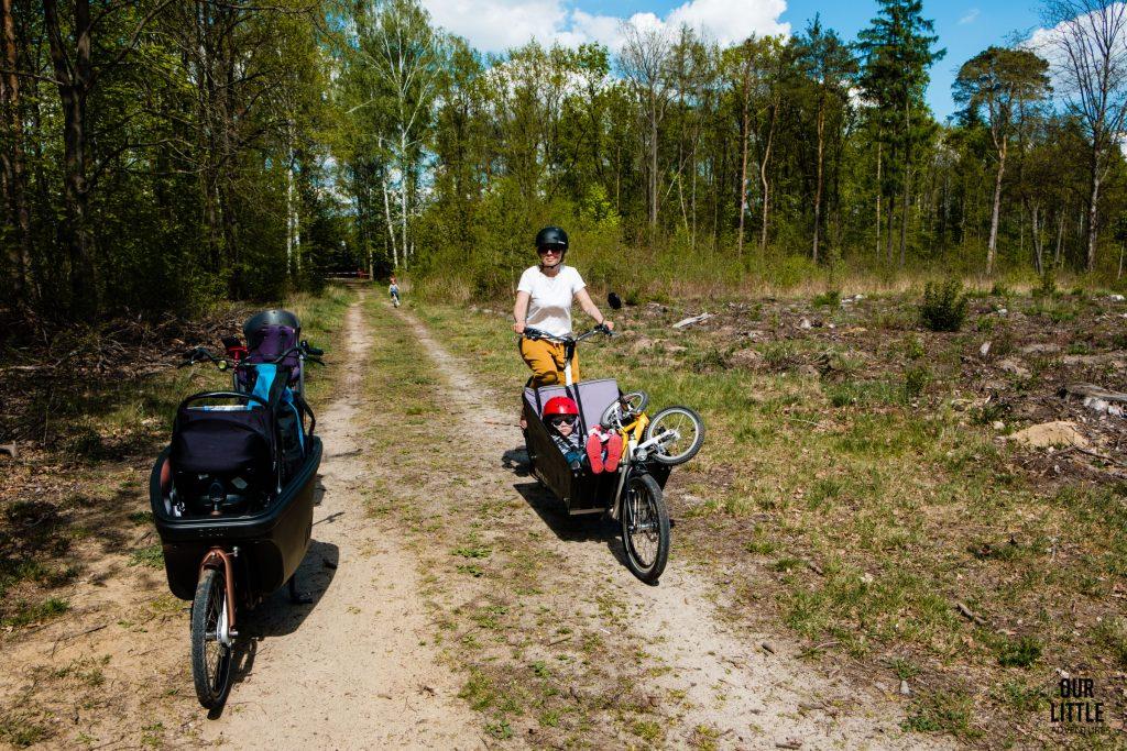 Karolina jedzie na rowerze cargo Stork a w skrzyni siedzi Jasio z rowerem Woom2 a obok stoi rower Dollybikes