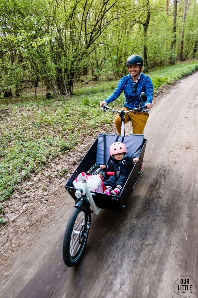 Karolina jedzie na rowerze cargo Stork a w skrzyni siedzi Basia