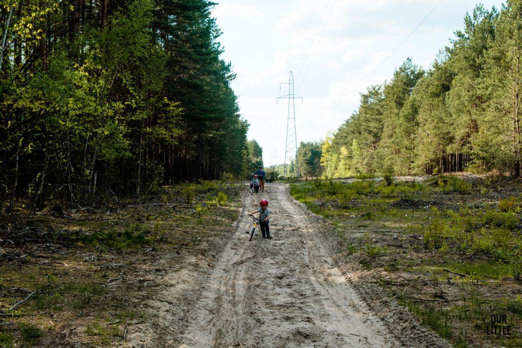 Jasio prowadzi rower przez piaszczyste tereny