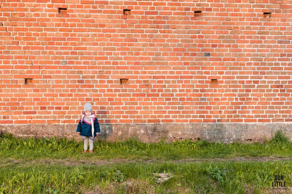 Mania stoi pod murem stodoły w Siedlisku Pasieka