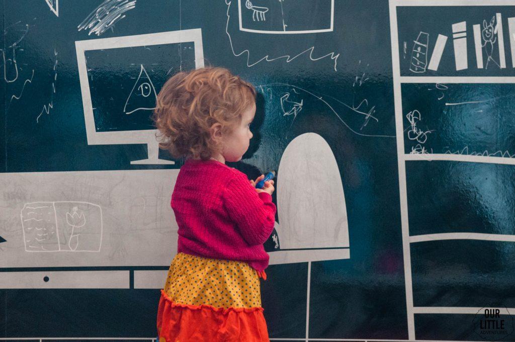 Marianka pisze po tablicy w Zachęcie