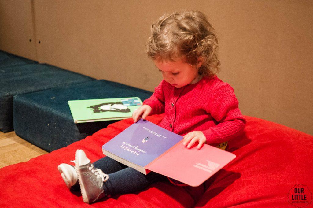 Marianka siedzi w Zachęcie i czyta książkę dla dzieci