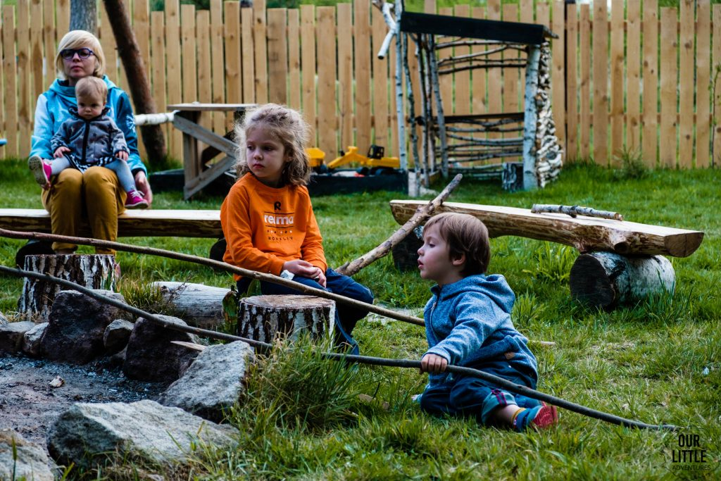 Dzieci pieką kiełbaski nad ogniskiem