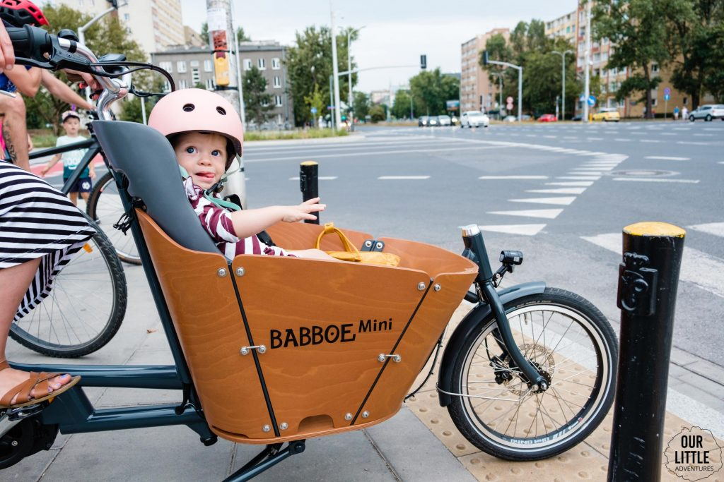 Dziecko siedzi w dodatkowej wkładce do roweru cargo Babboe Mini