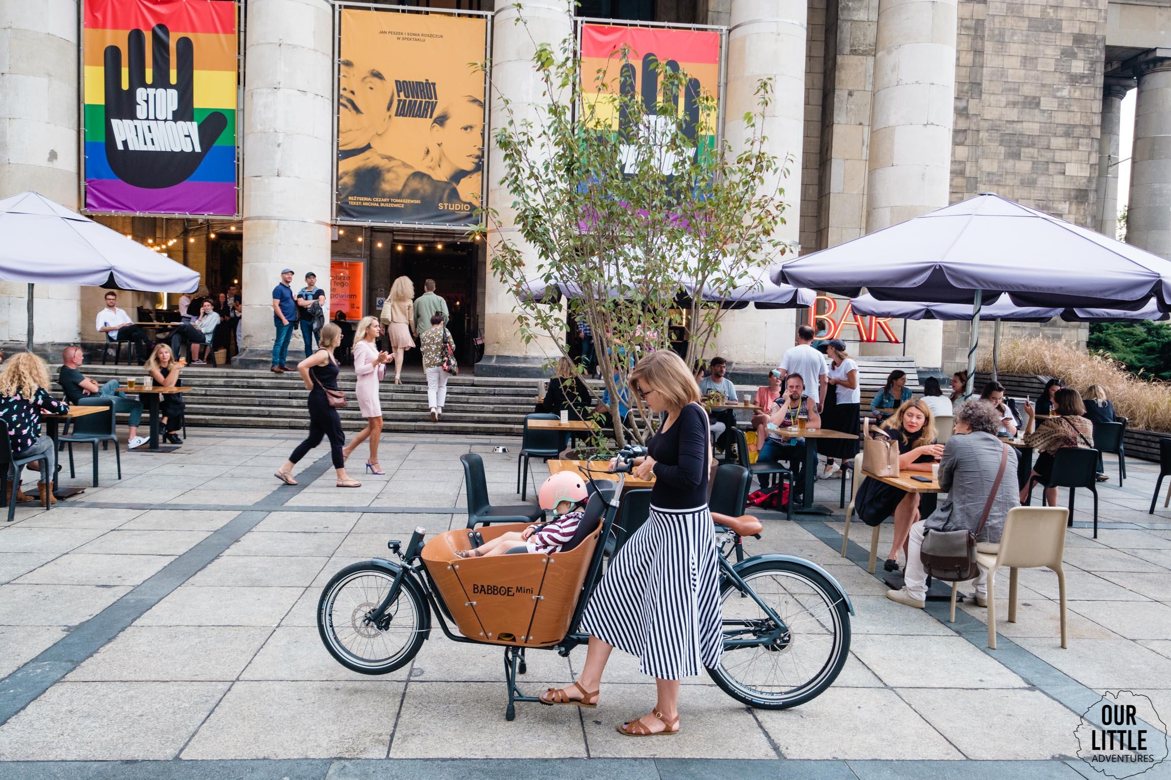 Kobieta stawia na nóżkę rower cargo Babboe Mini