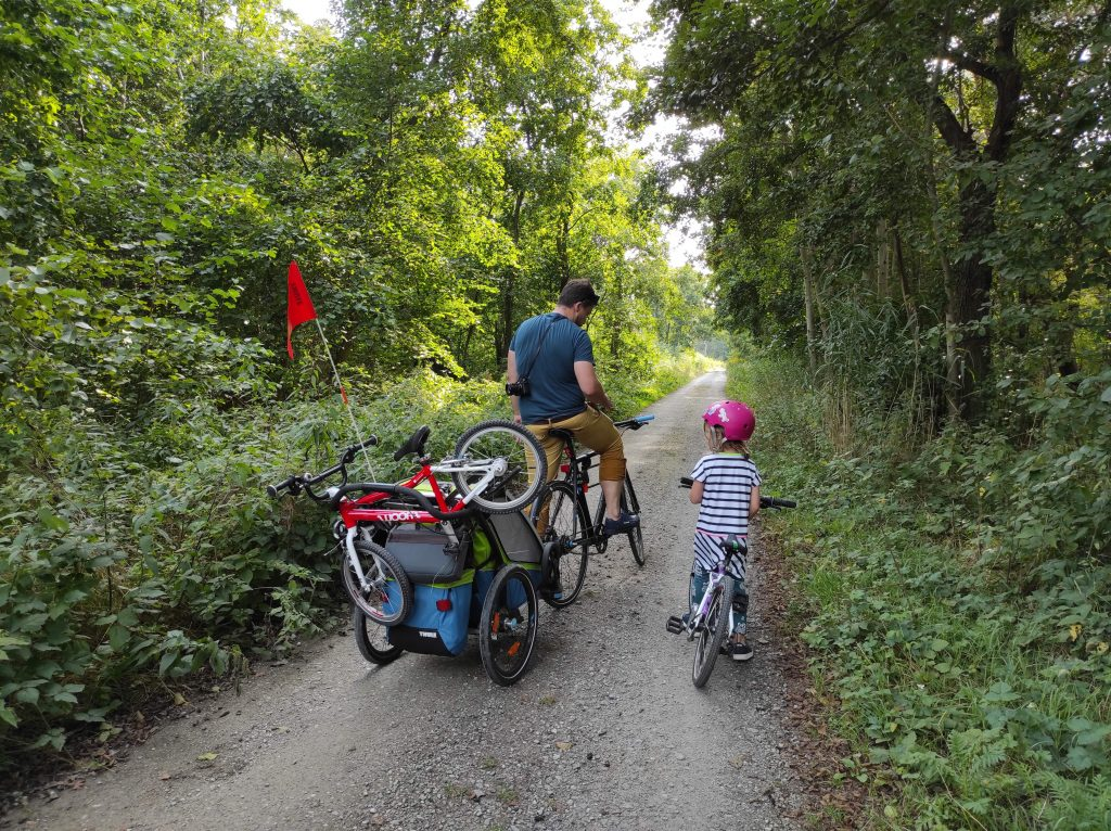Przyczepka rowerowa Thule Chariot Sport, rodzina na rowerach w lesie