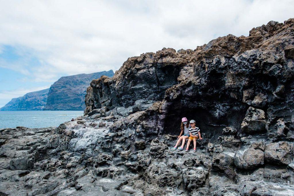 Dzieci siedzą na skałach w Los Gigantes, Teneryfa w czasie pandemii, Our Little Adventures