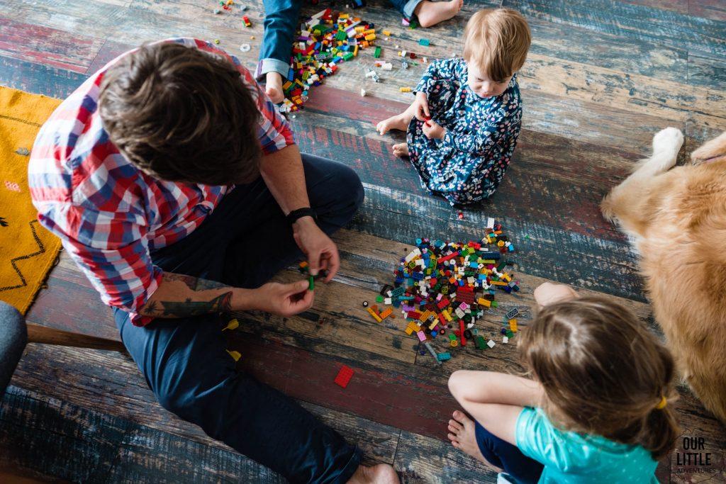 Dzieci na podłodze układają z tatą klocki