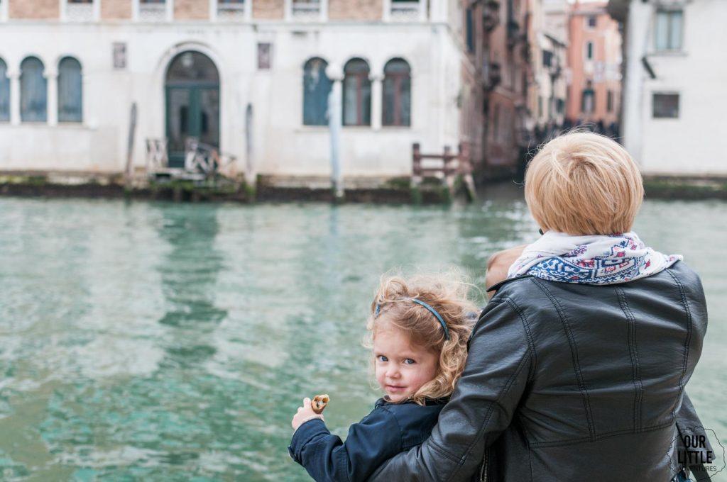 Dziecko z mama siedzi nad kanałem w Wenecji