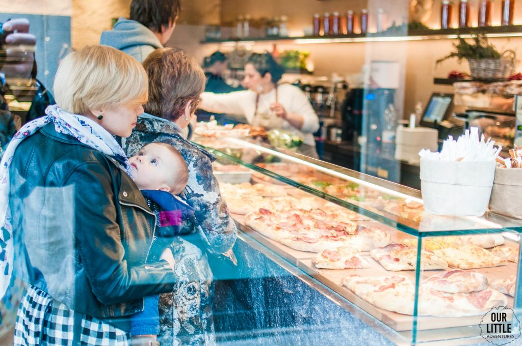 Mama z dzieckiem w nosidle w Wenecji stoi w kolejce w piekarni