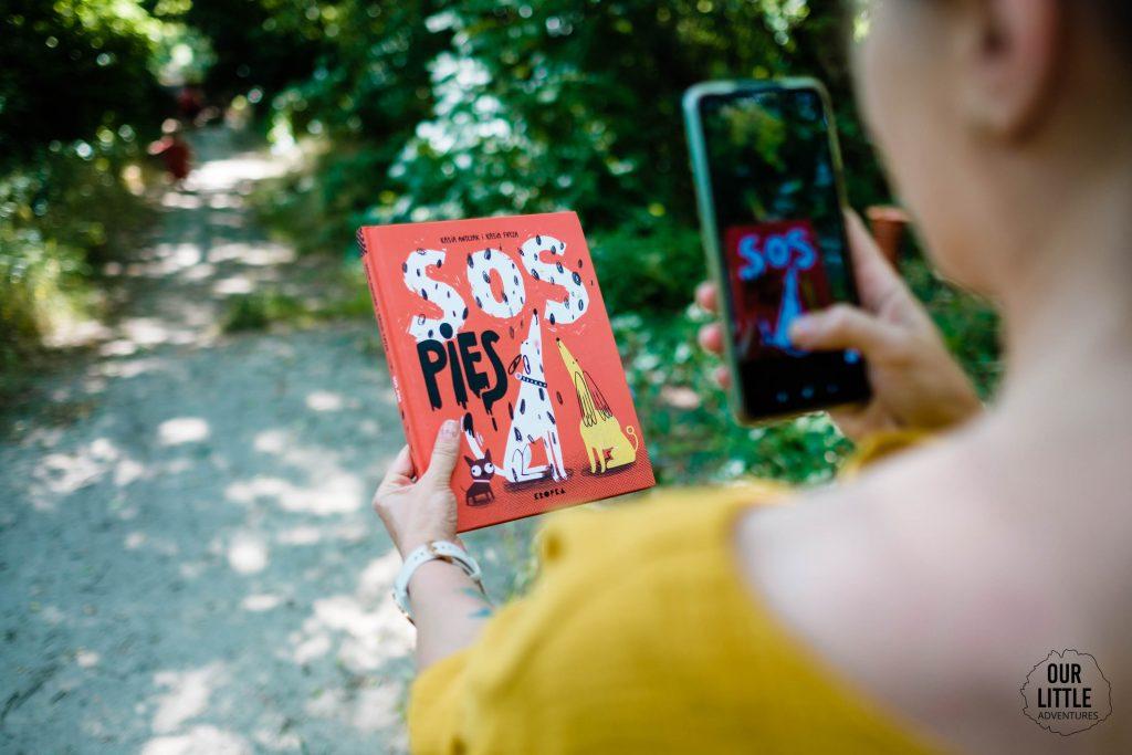 Książka SOS Pies trzymana przez kobietę, która robi jej zdjęcie telefonem - Our Little Adventures
