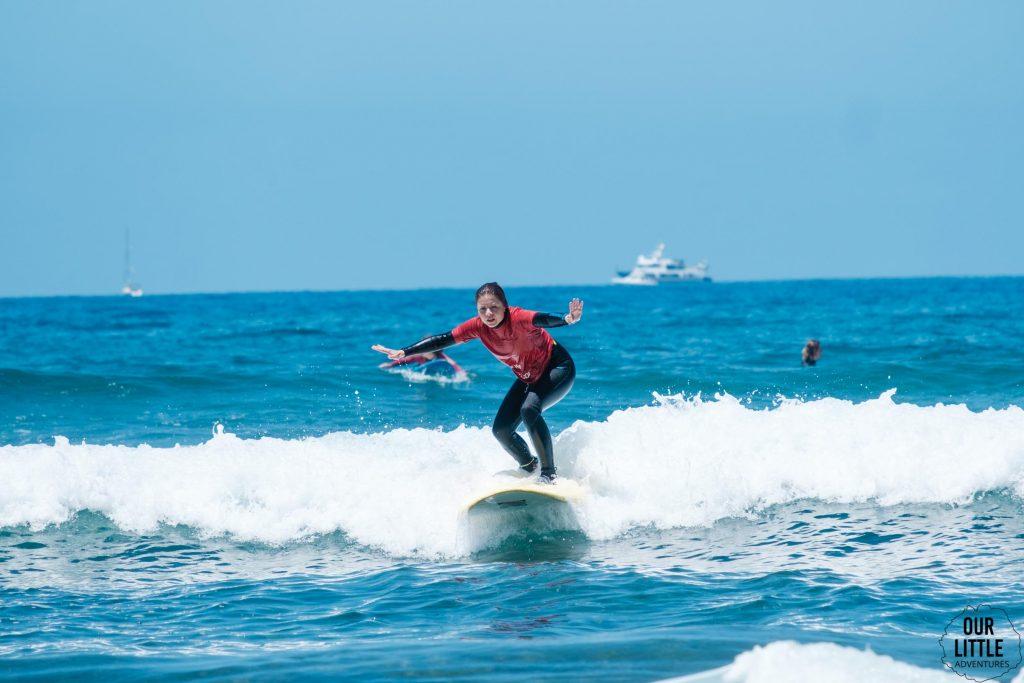 Kobieta uczy się na desce surfingowej na Teneryfie