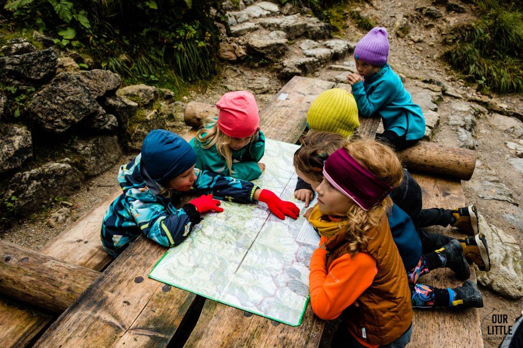 Dzieci siedzą przy stole na szlaku i czytają mapę, zdjęcie autorstwa OurLittleAdventures.pl