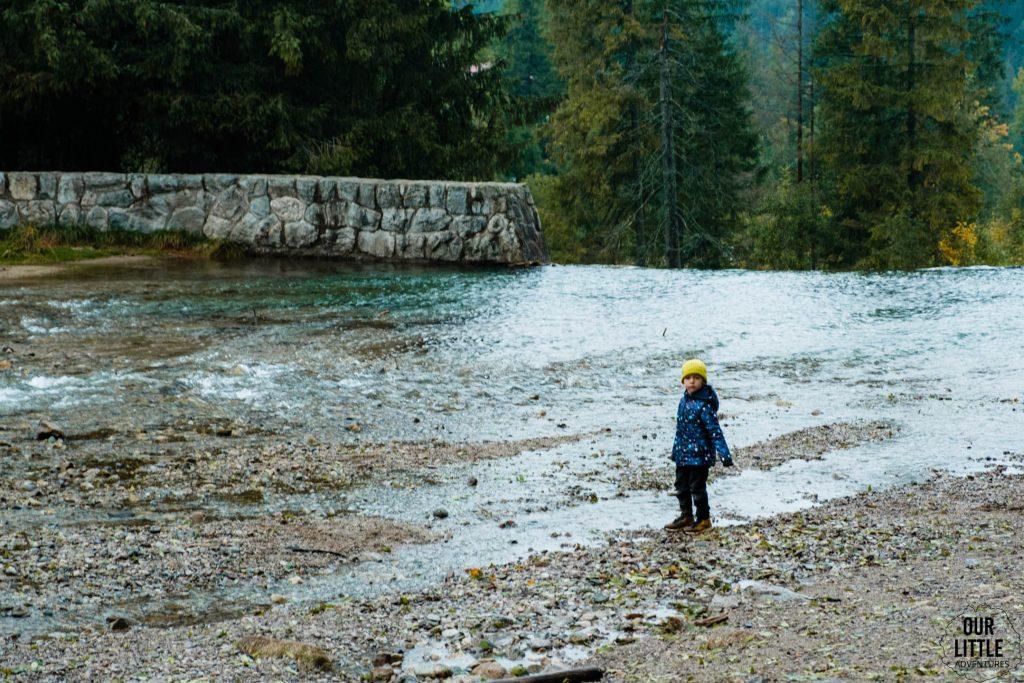 Dziecko stoi nad rzeką w Kużnicach, zdjęcie autorstwa OurLittleAdventures.pl