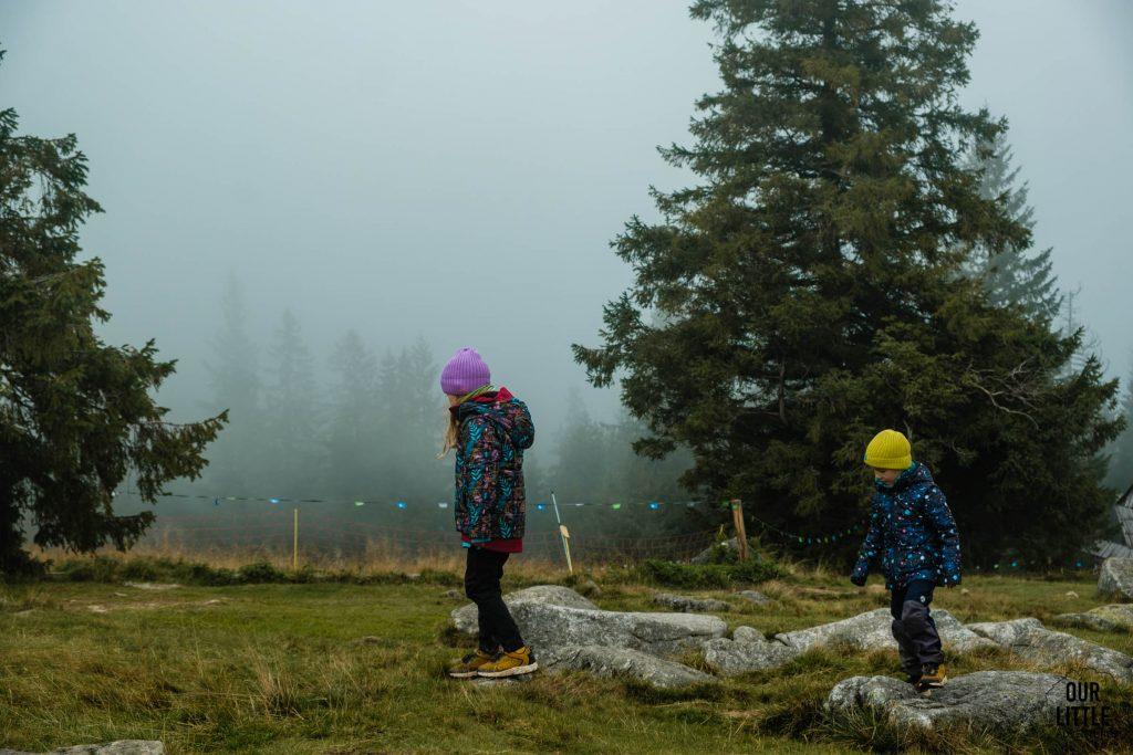 Dzieci skaczą po kamieniach na Rusinowej Polanie, wokół mgła, zdjęcie autorstwa OurLittleAdventures.pl