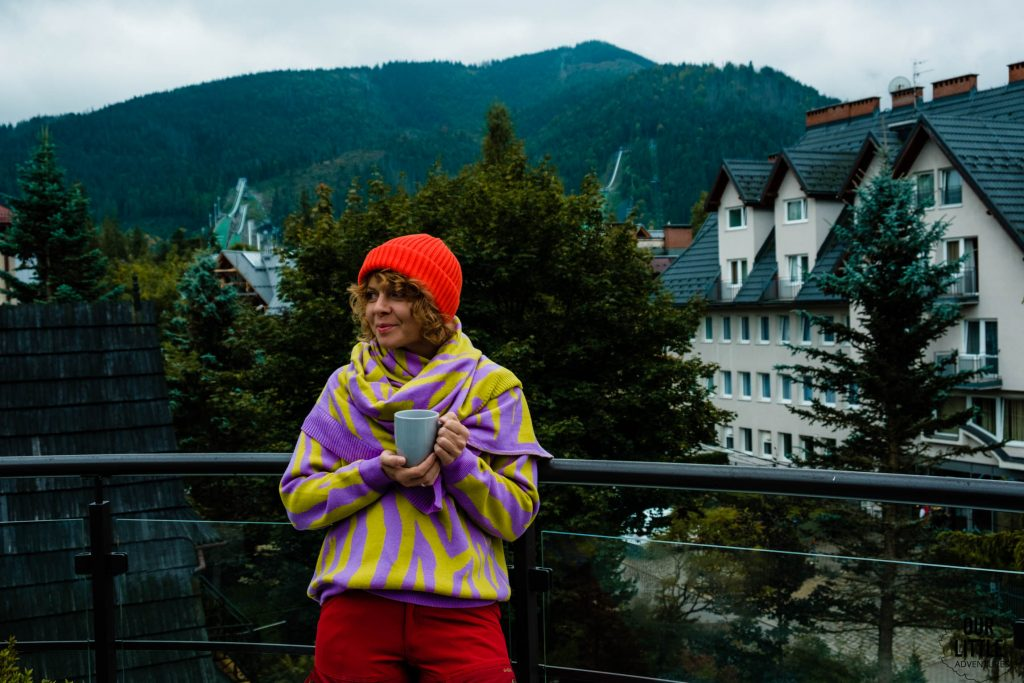 Kobieta stoi z kubkiem na balkonie z widokiem na Tatry, Zakopane, zdjęcie autorstwa OurLittleAdventures.pl