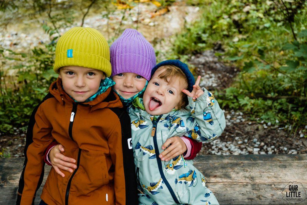 Troje uśmiechniętych dzieci siedzi na ławce na szlaku w Dolinie Strążyskiej, zdjęcie autorstwa OurLittleAdventures.pl