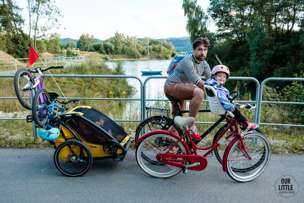 Ojciec z dziećmi w przyczepce i dwoma rowerami