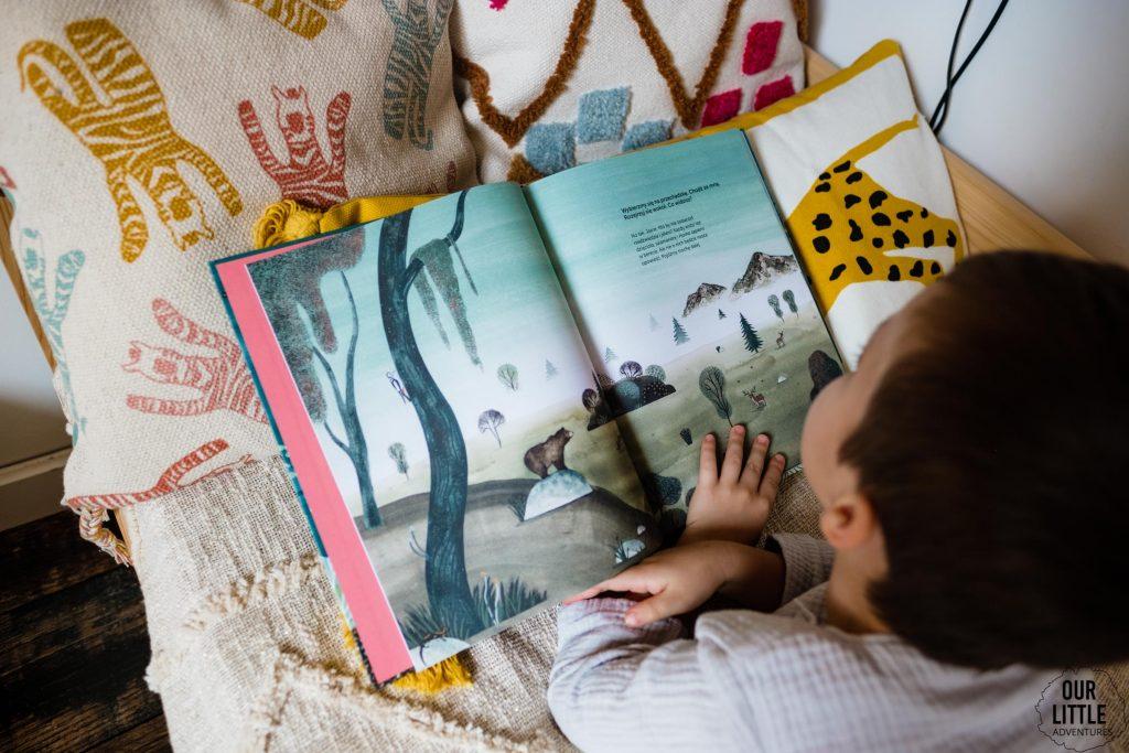 Chłopiec czytający książkę Milion ostryg na szczycie góry leży na łóżku - książki obrazkowe dla dzieci Znak Emotikon, zdjęcie autorstwa OurLittleAdventures.pl