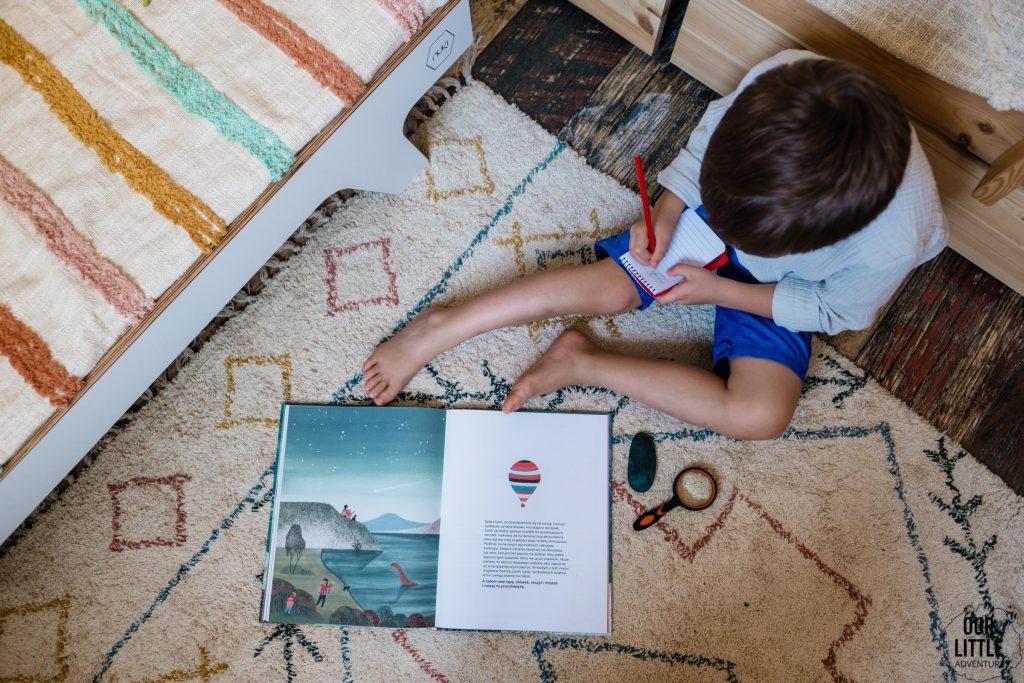 Książka Milion ostryg na szczycie góry leży na dywanie obok chłopca który pisze coś w notesie - książki obrazkowe dla dzieci Znak Emotikon, zdjęcie autorstwa OurLittleAdventures.pl